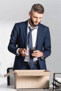 Kovulan işadamı, ofisindeki karton kutunun yanında kırtasiye malzemesi tutuyor.