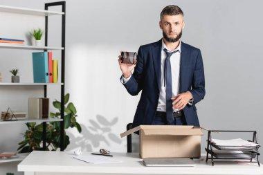 Kovulan işadamı karton kutu, dizüstü bilgisayar ve kağıtları masanın üzerinde tutuyor.
