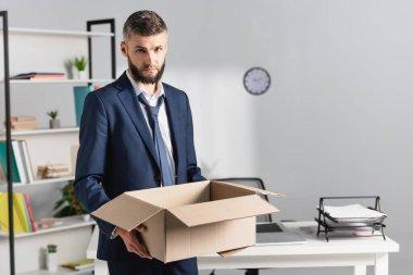 Kovulan işadamı, arka planda bulanık ofis masası olan karton bir kutu tutuyor.
