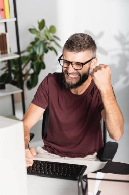 Nervous businessman with hand in fists looking at computer monitor near papers on blurred foreground in office stock vector