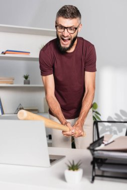 Screaming businessman beating laptop with baseball bat on blurred foreground in office stock vector