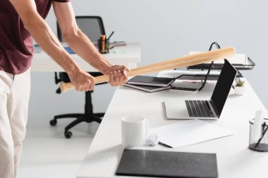 Cropped view of businessman beating laptop with baseball bat near paper folder on blurred foreground