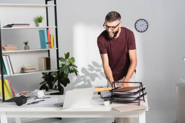 Angry businessman beating laptop with baseball bat near stationery on office table stock vector