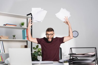 Screaming businessman throwing papers near laptop on blurred foreground in office stock vector