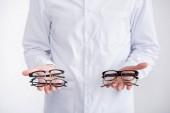 Ausgeschnittene Ansicht des Arztes, die Brillenpaare auf Handflächen zeigt, isoliert auf weiß