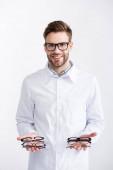 Vorderansicht eines lächelnden Arztes im weißen Mantel, der Brillenpaare auf Handflächen zeigt, während er die Kamera isoliert auf Weiß betrachtet