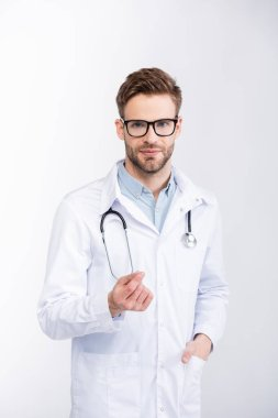Positive ophthalmologist with hand in pocket wearing eyeglasses and looking at camera isolated on white stock vector