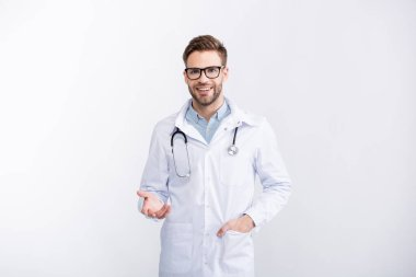 Front view of cheerful ophthalmologist with hand in pocket, wearing eyeglasses and gesturing isolated on white