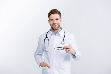 Front view of smiling ophthalmologist with hand in pocket holding eyeglasses, while looking at camera isolated on white stock vector