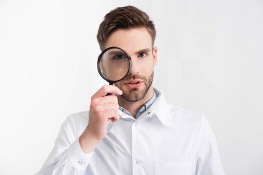 Portrait of confident ophthalmologist looking through loupe isolated on white stock vector