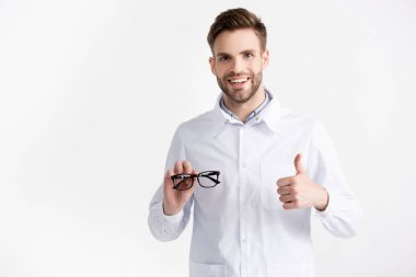 Front view of cheerful ophthalmologist with thumb up, showing eyeglasses isolated on white stock vector