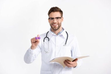 Front view of smiling doctor with folder showing lenses container isolated on white stock vector