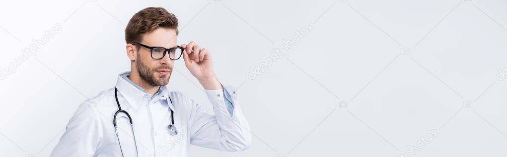 Confident doctor with stethoscope holding eyeglasses frame, while looking at camera on grey background, banner stock vector