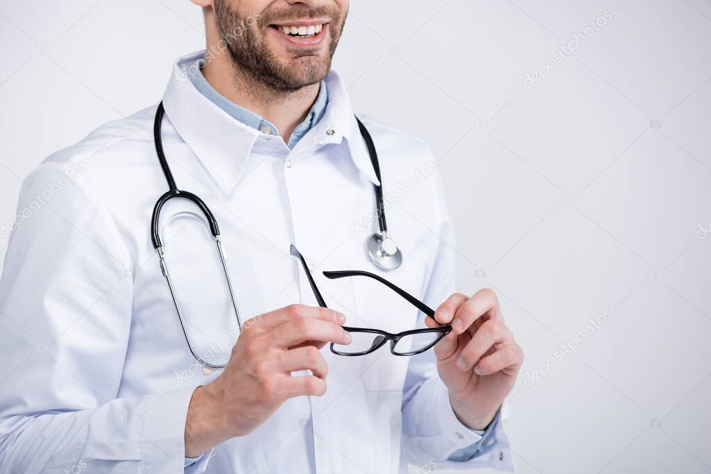Cropped view of smiling ophthalmologist with stethoscope holding eyeglasses isolated on white stock vector