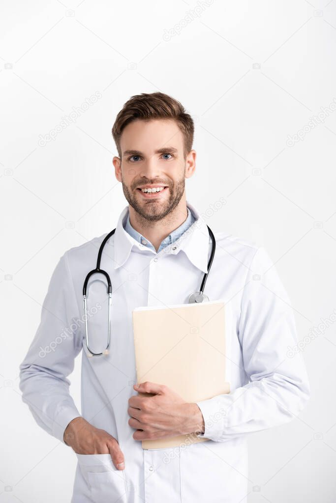 Front view of smiling ophthalmologist with hand in pocket holding folder, while looking at camera isolated on white stock vector