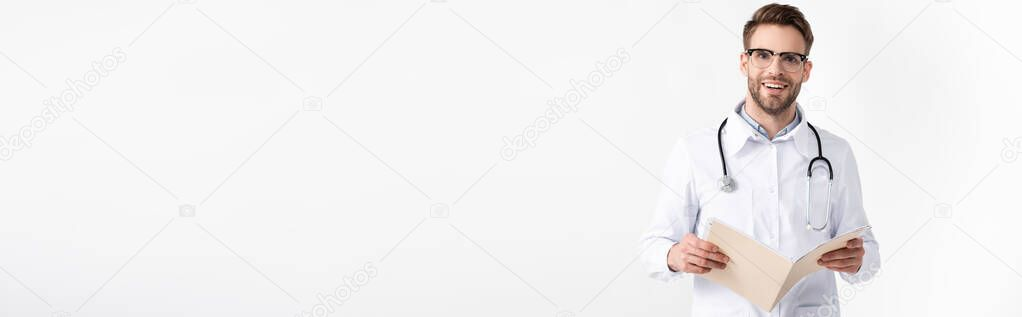 Happy young adult ophthalmologist with stethoscope holding folder isolated on white, banner stock vector