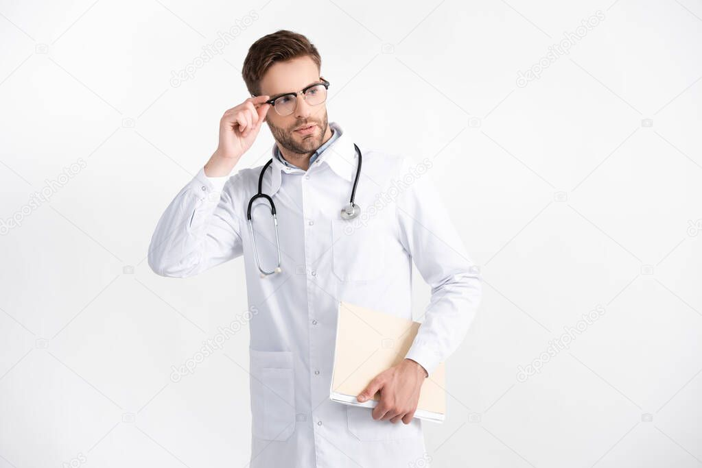 Young adult doctor with folder holding eyeglasses frame, while looking away isolated on white stock vector