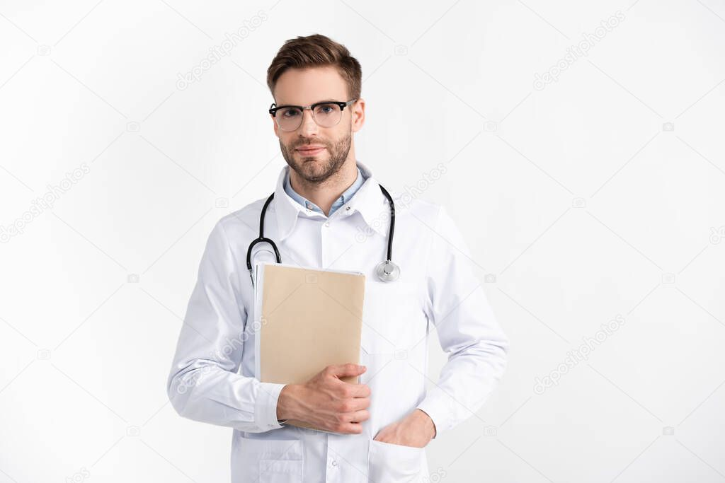 Front view of positive doctor with hand in pocket, holding folder, while looking at camera isolated on white stock vector