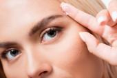 Oříznutý pohled na ženu dívající se do kamery při držení kontaktní čočky izolované na bílém
