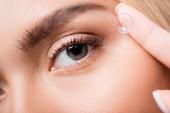 Zblízka pohled na ženu držící kontaktní čočku poblíž oka