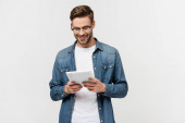 Smiling man in eyeglasses holding digital tablet isolated on grey