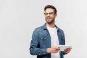 Usmívající se muž v brýlích drží digitální tablet izolované na šedé