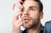 Mladý muž vkládající kontaktní čočky do očí izolovaných na šedé