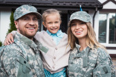 Happy father and mother in military uniforms lifting daughter and looking at camera on blurred background