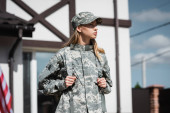Confident military servicewoman with backpack looking away with blurred house on background