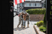 Daughter hugging mother and father in military uniforms on street near house on blurred foreground