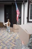 Dívka nesoucí kartónovou krabici k domu na rozmazaném popředí