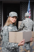 Blonde woman in camouflage holding cardboard box and looking at camera with blurred military man on background