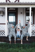 Photo Happy family with hands in air sitting on house threshold on backyard