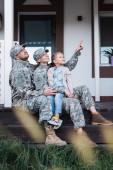 Šťastná vojenská matka a otec ukazuje prstem, dívá se jinam, sedí s dcerou na prahu domu na rozmazané popředí