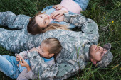 Overhead view of military serviceman resting and embracing wife and daughter, while lying on grass