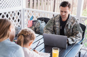 Military serviceman with necklace using laptop, while sitting at table with blurred woman and daughter on foreground