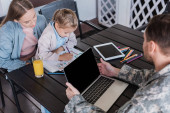 Military serviceman using laptop and looking at girl sitting with woman and drawing with colorful pencils at table