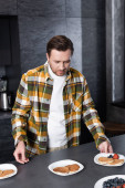 Bearded man in checkered shirt serving plates with pancakes and fruits in loft kitchen