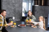 Fröhliche Familie prostet mit Gläsern Saft zu, während sie am Tisch mit Obst und Pfannkuchen in der Küche sitzt
