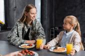 Usmívající se matka a dcera s sklenicemi džusu dívají na sebe, zatímco sedí u stolu s palačinkami v kuchyni