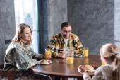 Šťastný pár snídá, směje se, zatímco sedí u stolu v kuchyni s rozmazanou dívkou na popředí