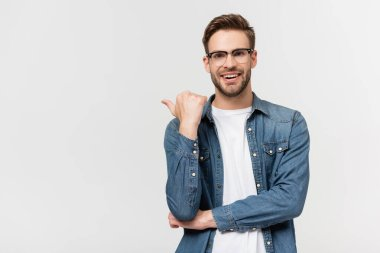 Smiling man in eyeglasses pointing with finger isolated on grey stock vector