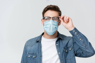 Young man in medical mask touching misted eyeglasses isolated on grey stock vector