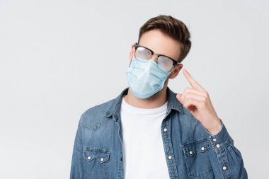 Young man in medical mask pointing with finger at misted eyeglasses isolated on grey stock vector