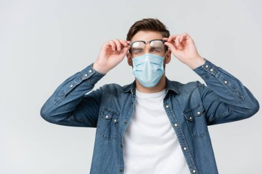 Young man in medical mask holding misted eyeglasses isolated on grey stock vector