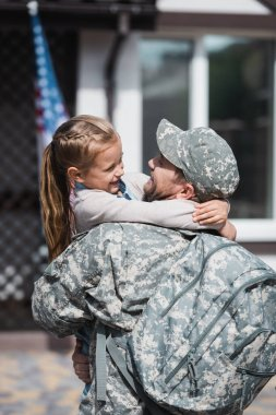 Happy father in military uniform hugging daughter on blurred background stock vector