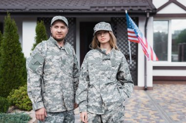 Military couple in uniforms standing together and looking at camera near house stock vector