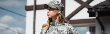 Confident military servicewoman looking away on blurred background, banner stock vector
