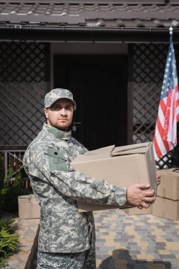 Military man holding cardboard box, while looking at camera near house and american flag stock vector