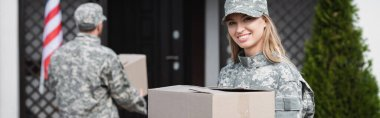Happy military servicewoman holding cardboard box and looking at camera with blurred man on background, banner stock vector